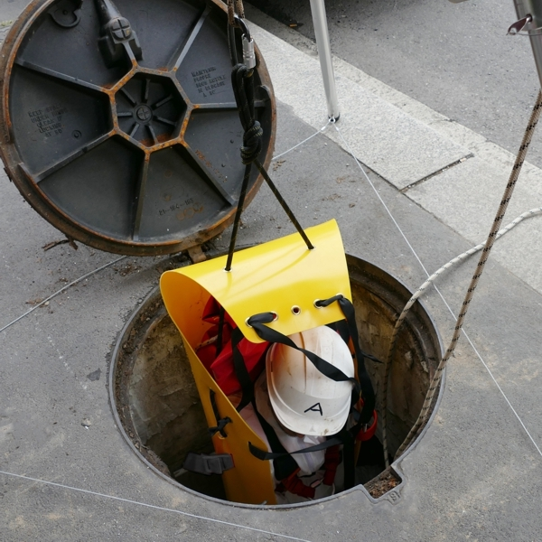a casualty being raised out of a manhole using a yellow stretcher